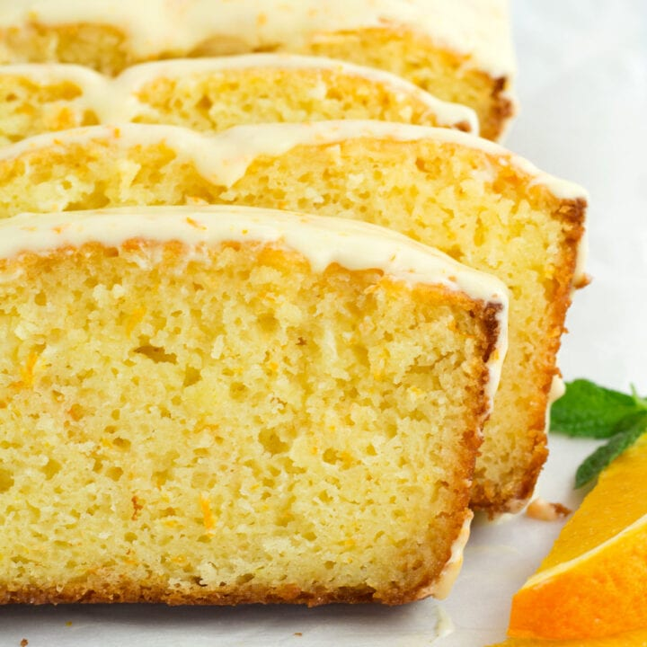 Staggered slices of orange loaf cake with glaze dripping off sides.