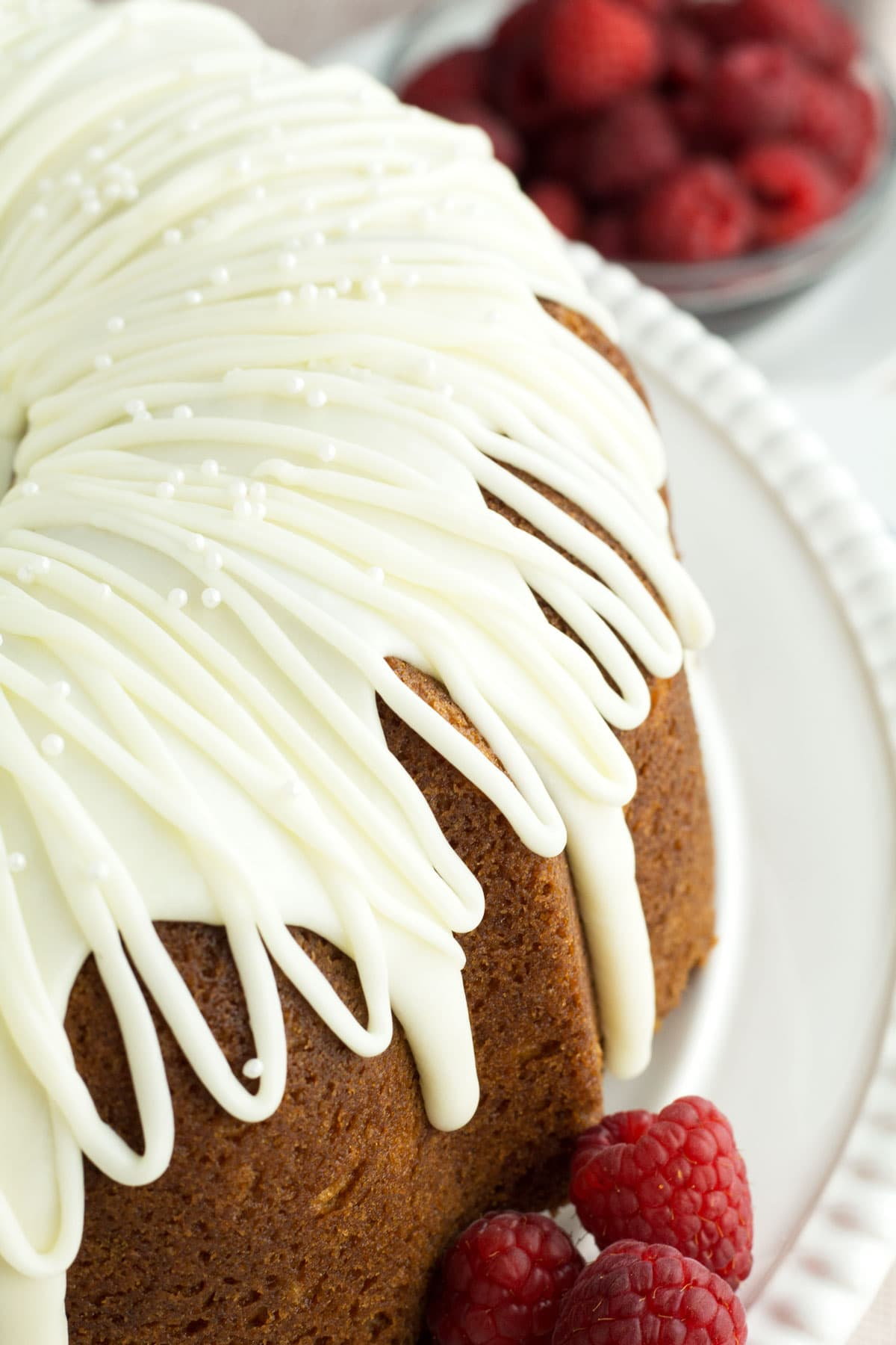 Beautiful white chocolate frosting with edible pearls decorating a bundt cake.