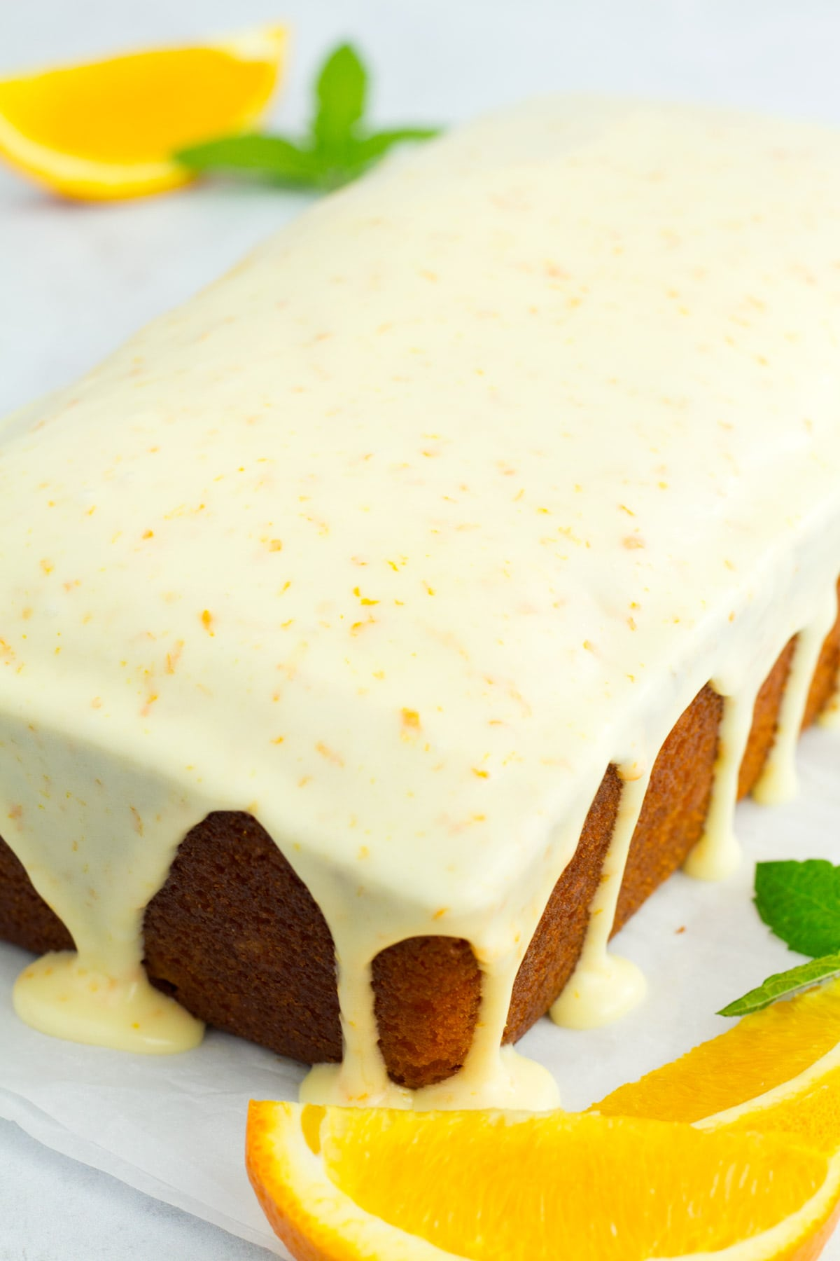 Whole orange loaf cake with glaze dripping down the sides.