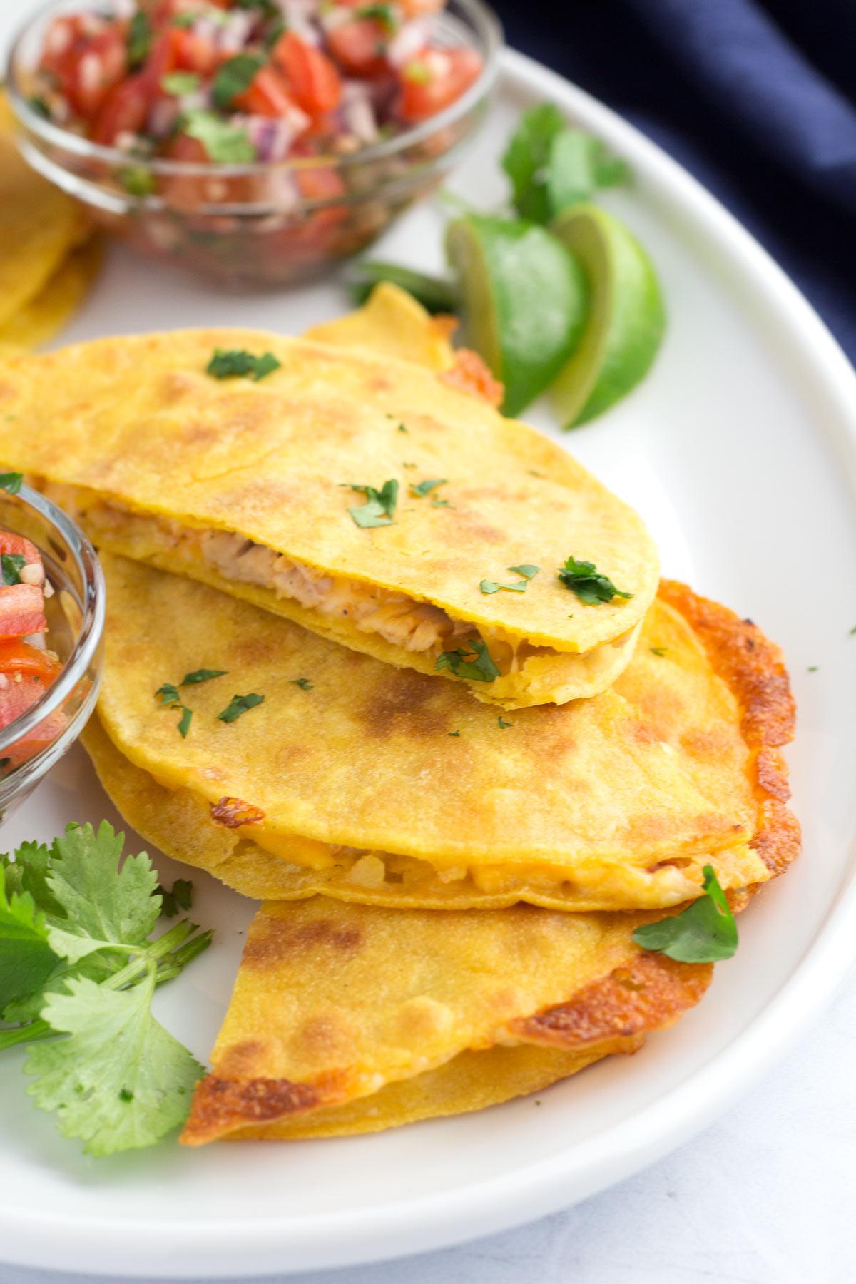 Half pieces of a quesadilla made with corn tortillas on a platter with pico de gallo.
