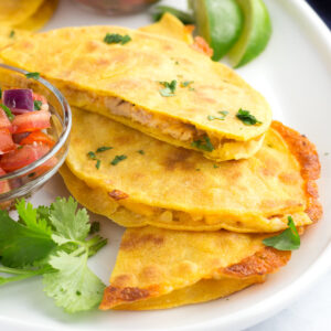 Three pieces of taco quesadillas made layered on a plate with fresh salsa and limes.