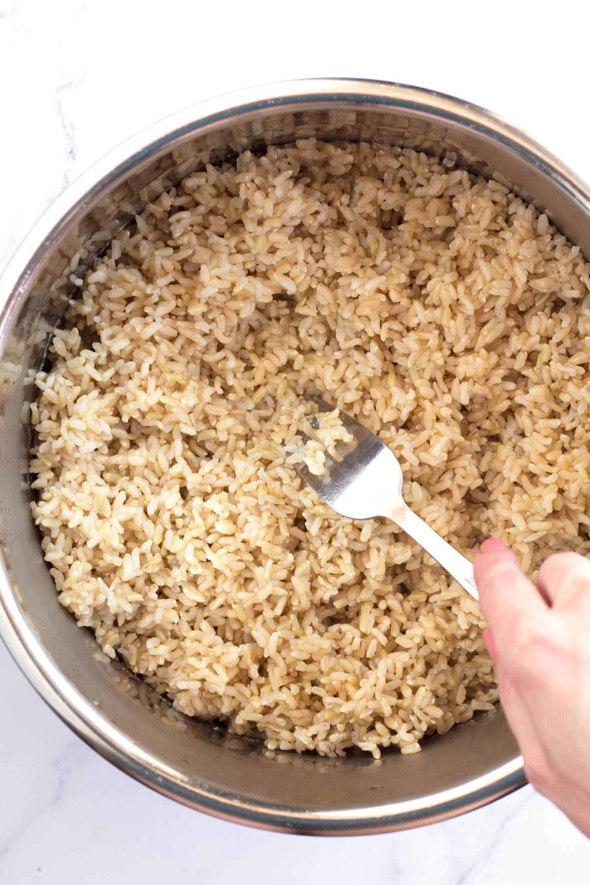 Using a fork to fluff rice before freezing.