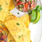 Platter filled with taco quesadillas and fresh pico de gallo and a blue towel.