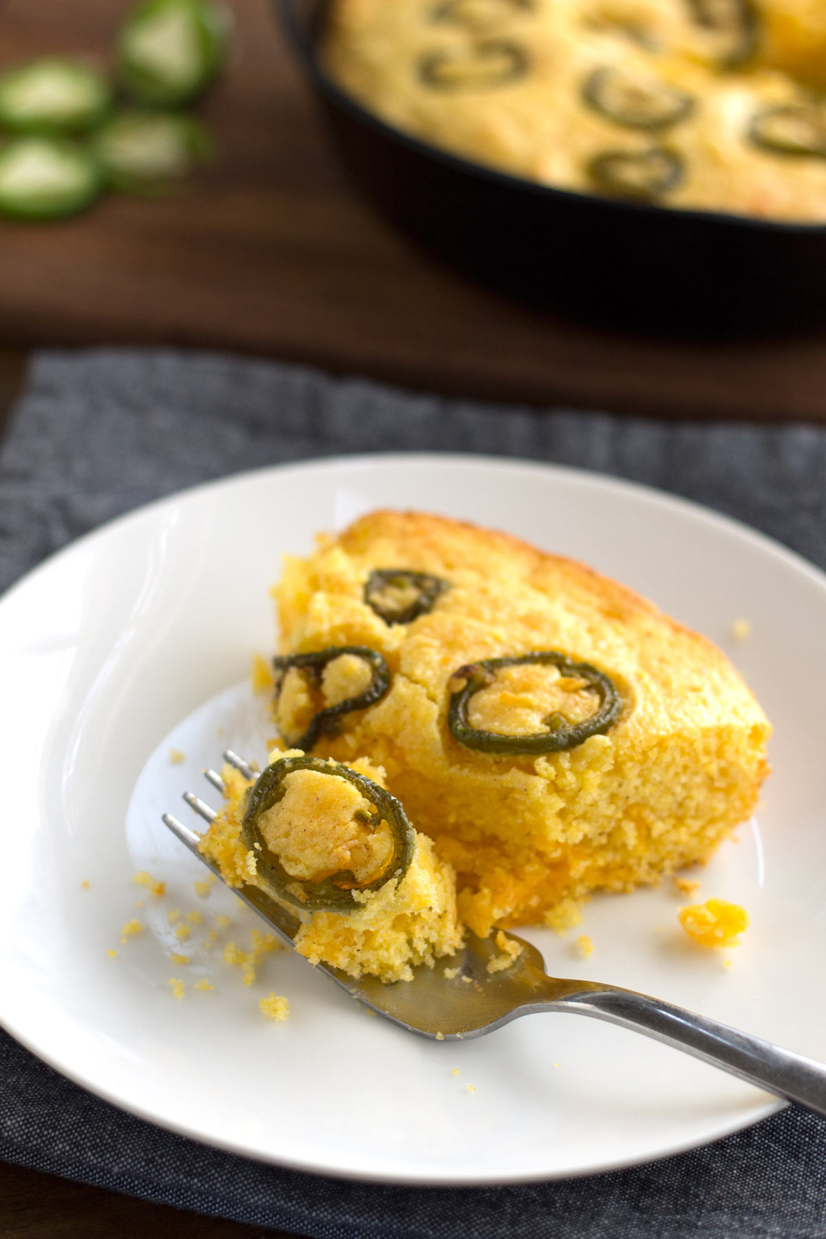 Piece of Mexican-style jalapeno cornbread on a plate with a fork.