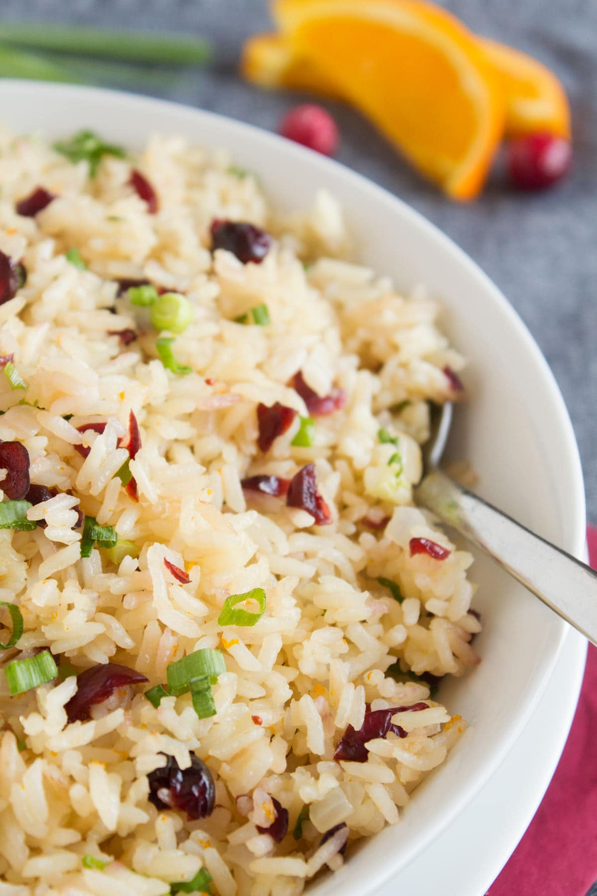 Citrus rice with cranberries and orange slices in the background.