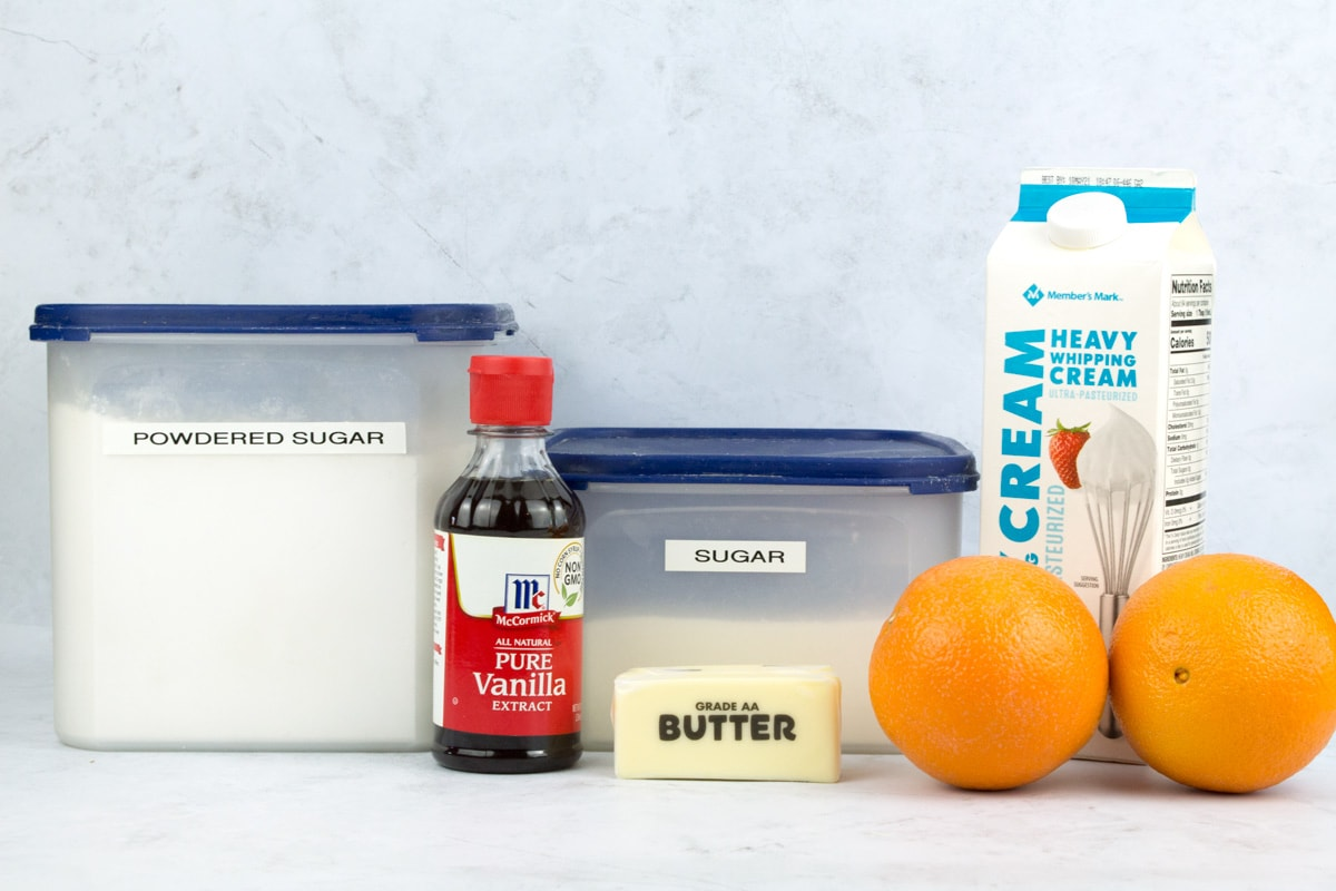 Ingredients for orange cake icing on white countertop.