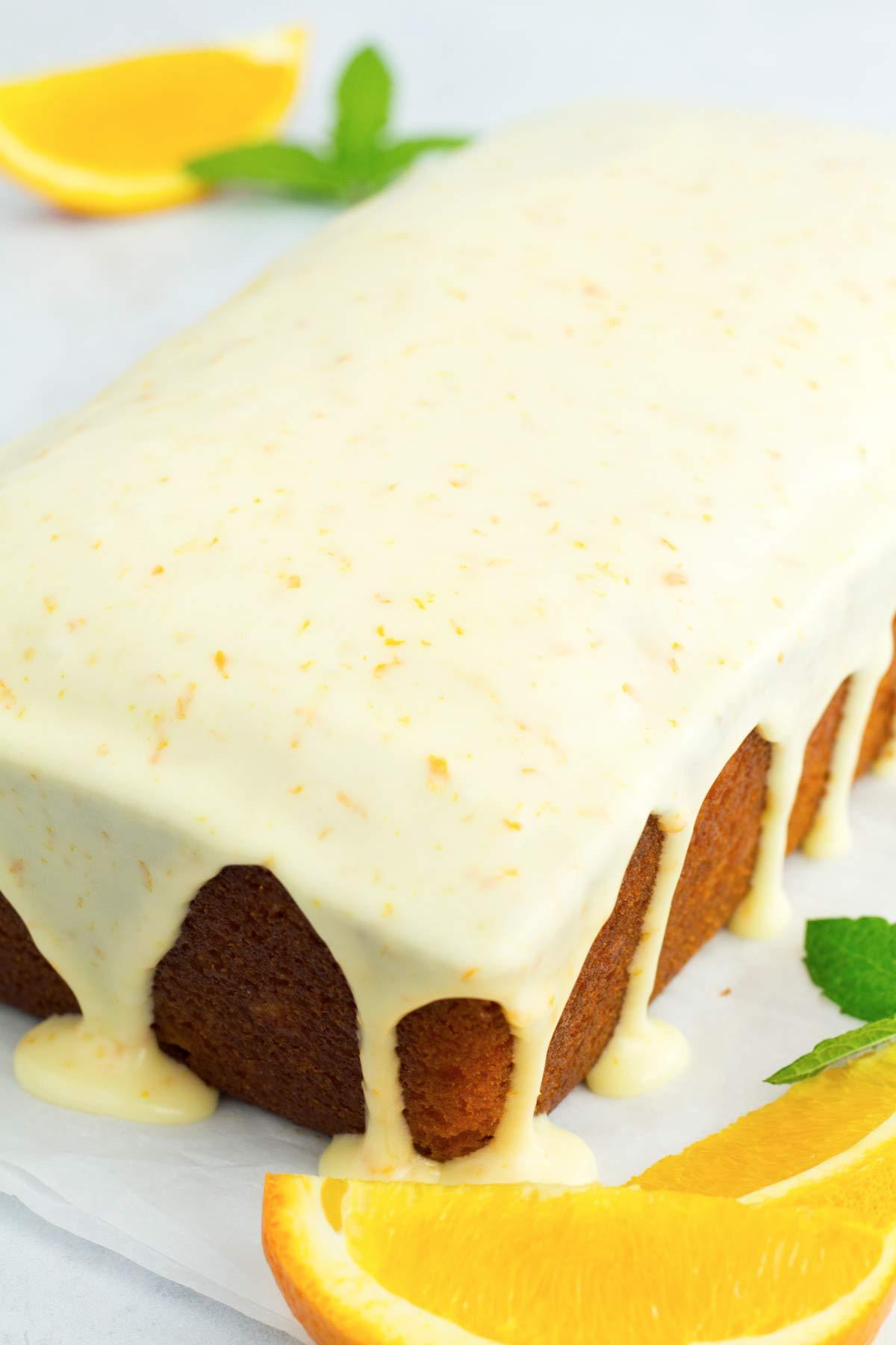Whole orange cake with orange glaze icing dripping down the sides.