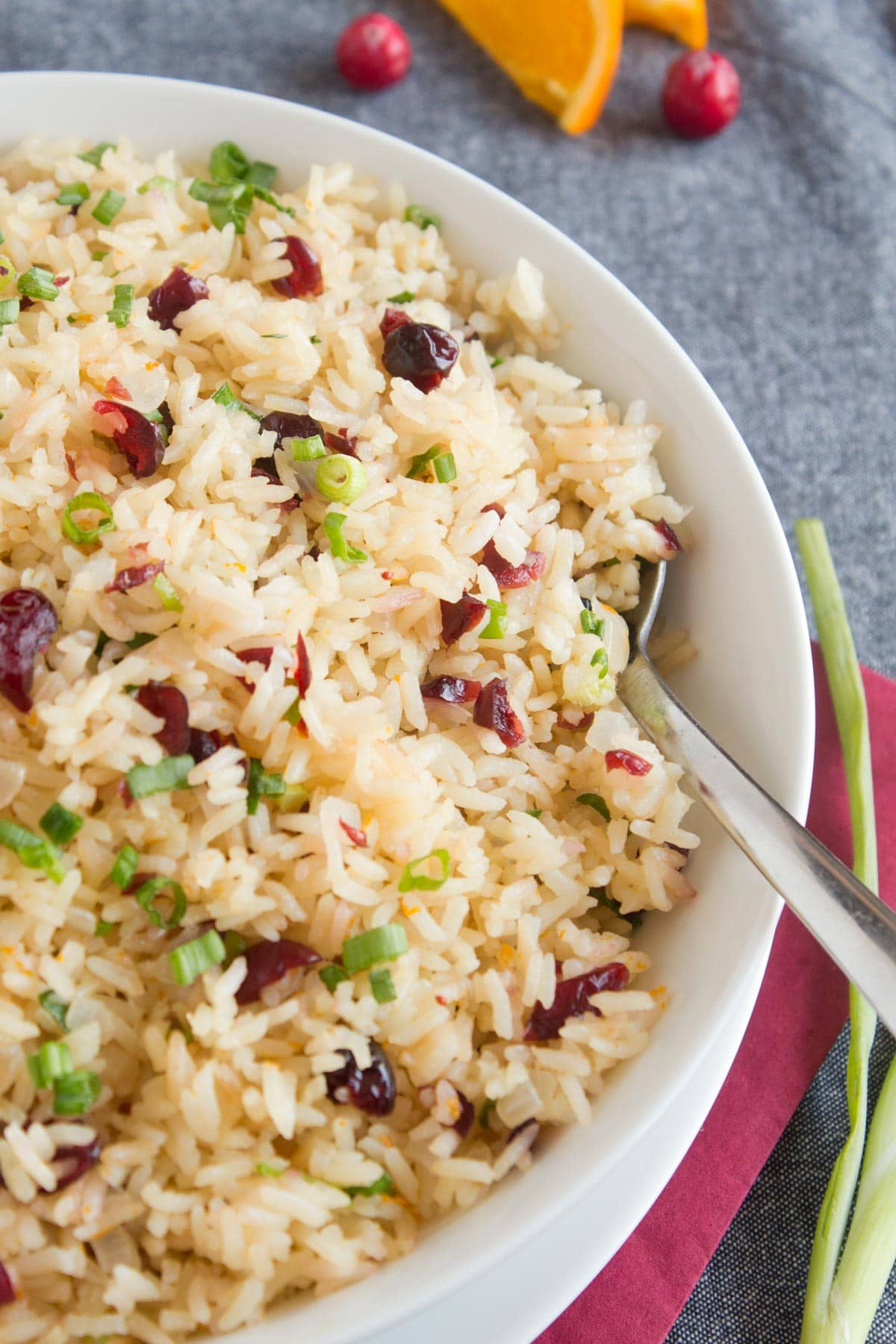 White rice made with orange juice and cranberries in white bowl.