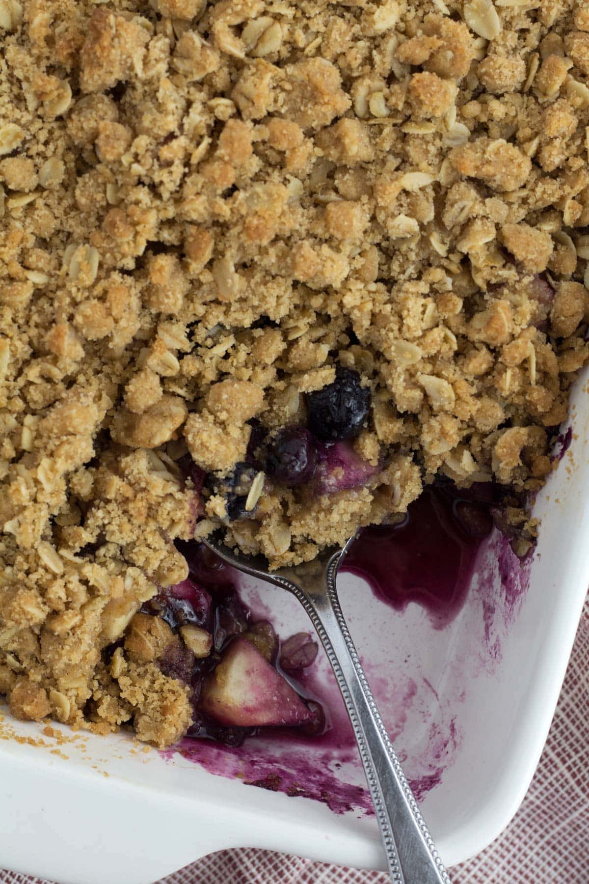 Spoon scooping golden brown crumble topping and baked fruit.
