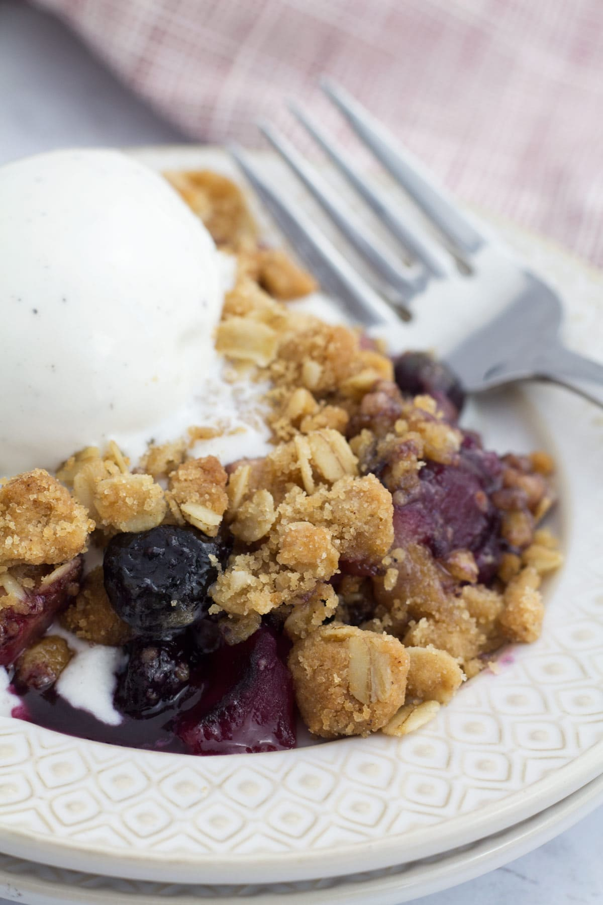 Small plate with apple and blueberry crumble, ice cream, and a fork.