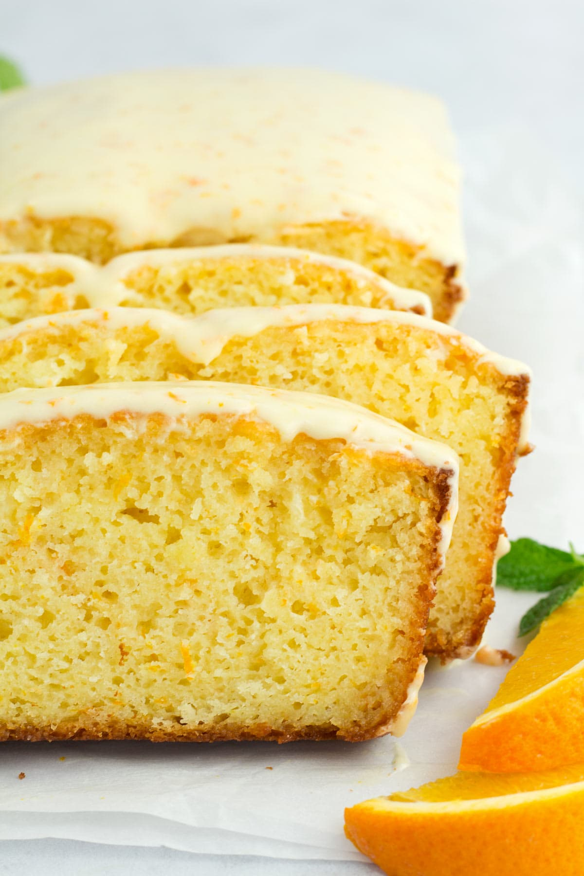 Slices of loaf cake with fresh orange icing on top.