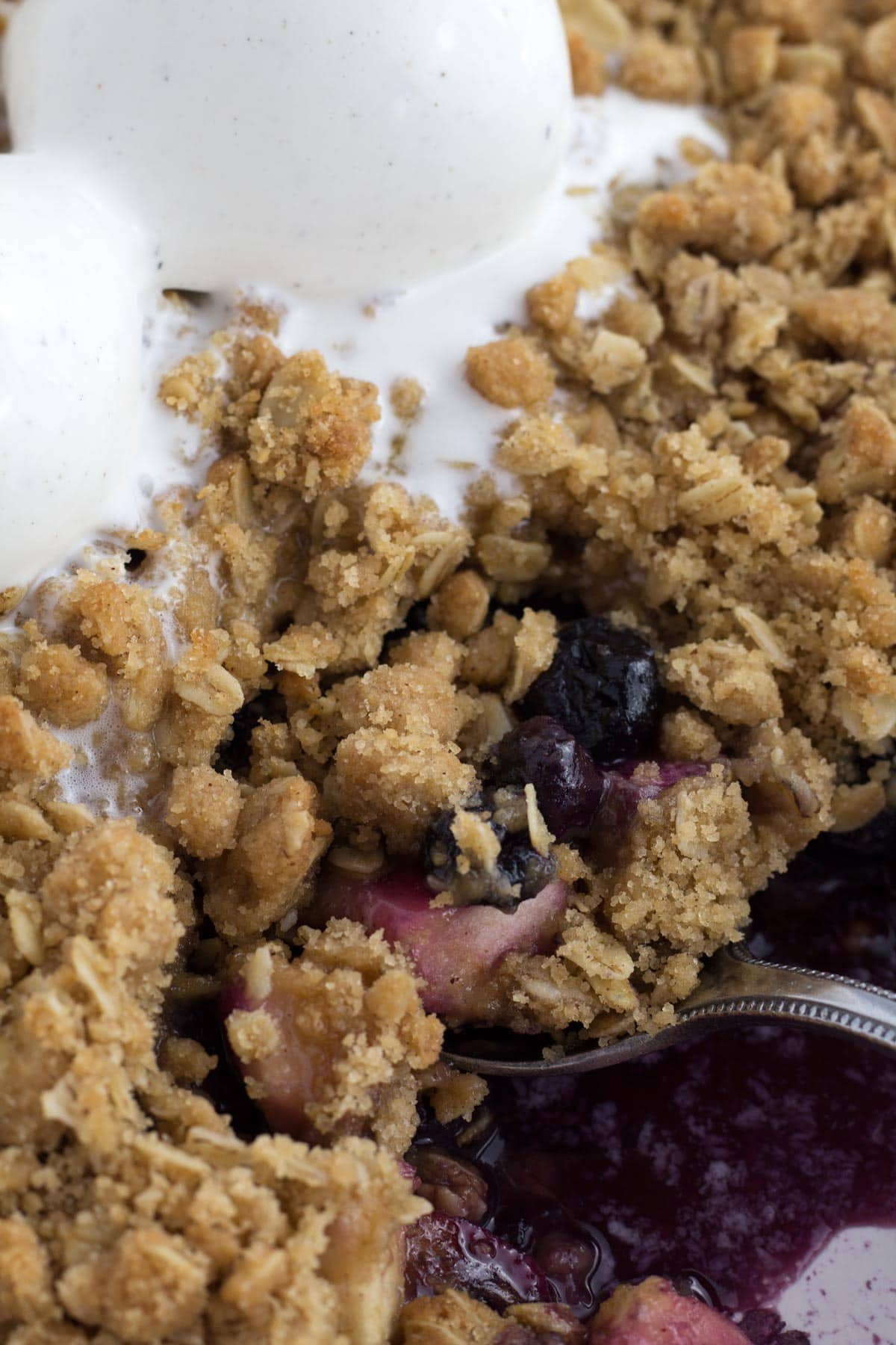Very close view of spoon scooping blueberry and apple crumble out of pan.