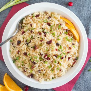 Orange rice with cranberries and scallions in white bowl on top of red and gray napkins.