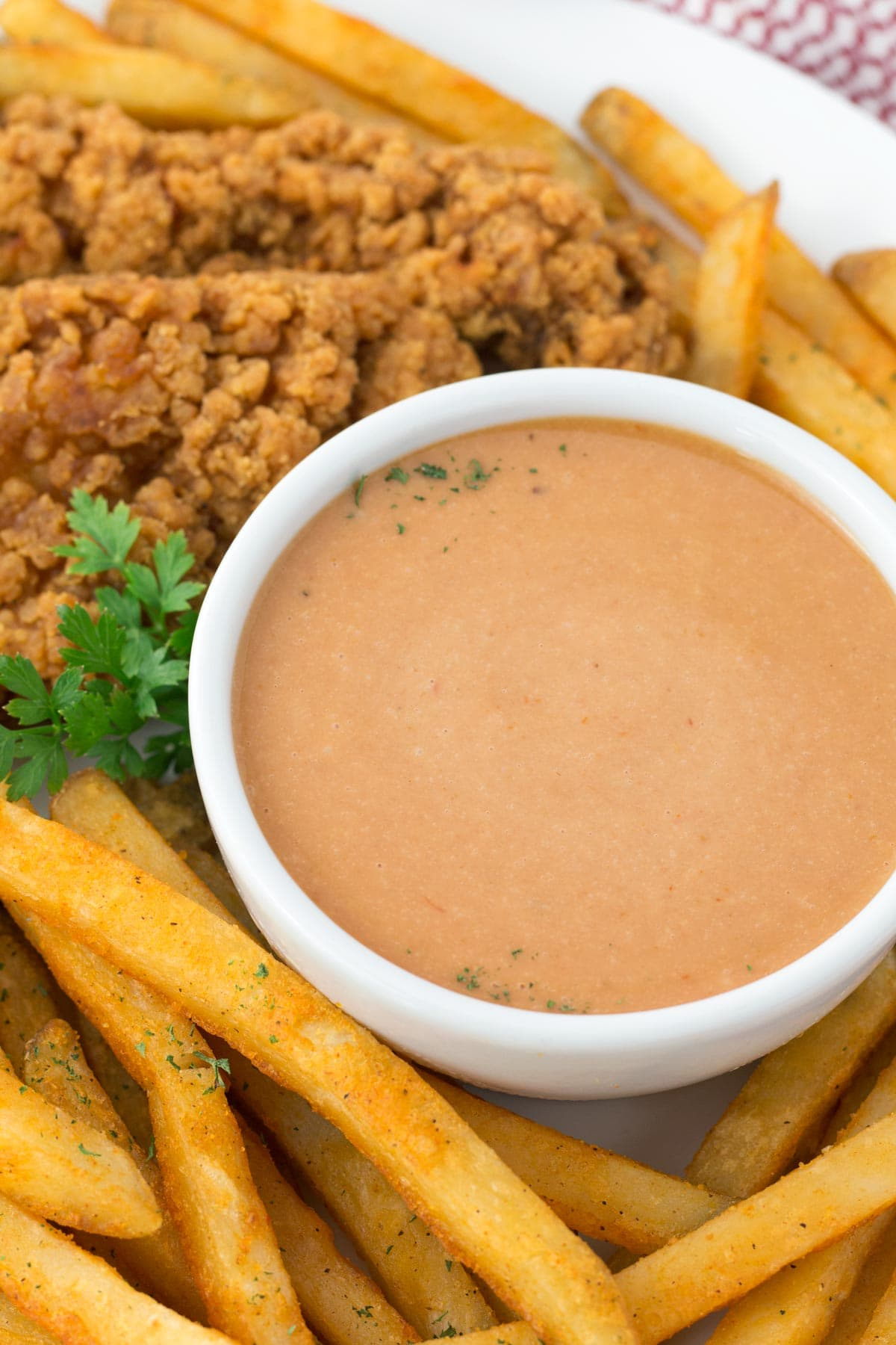 Bowl of Red Robin dipping sauce surrounded by fries and chicken tenders.