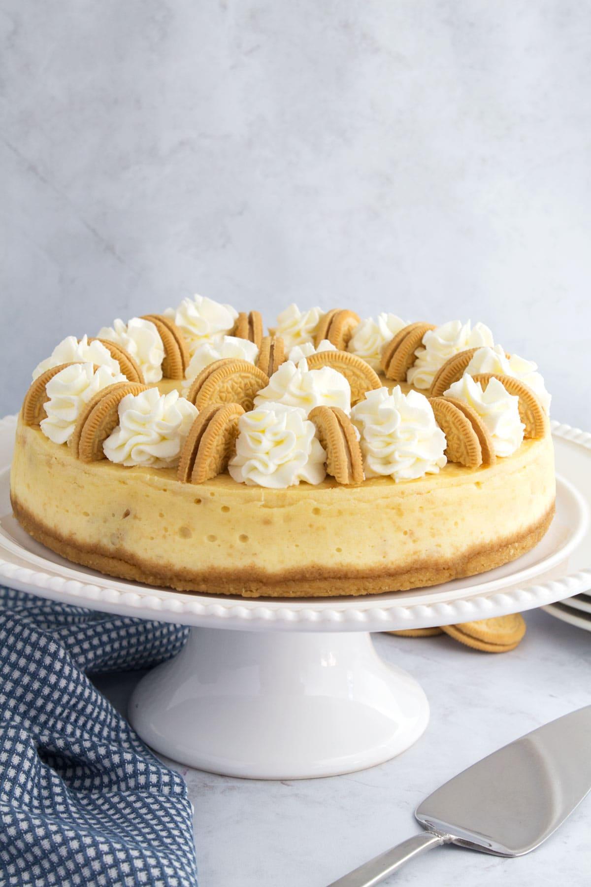 Whole white oreo cheesecake on white cake stand.