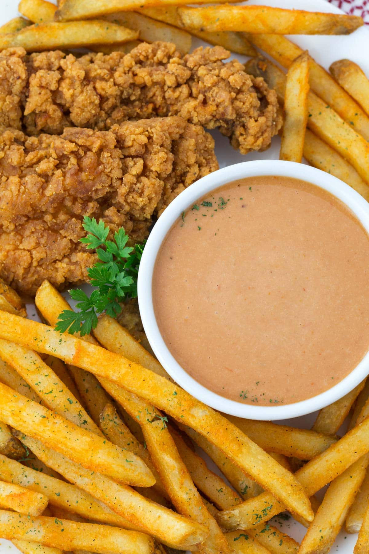 Overhead view of platter of french fries and bowl of Red Robin onion ring sauce.
