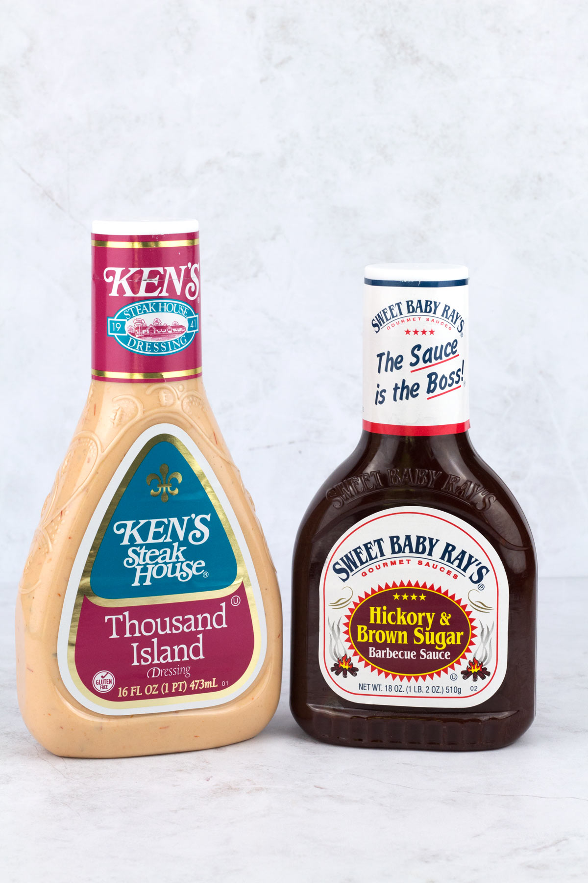 Bottles of Thousand Island dressing and barbecue sauce on counter.