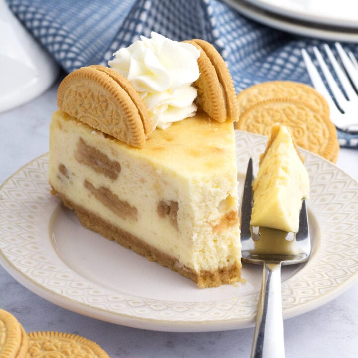 Slice of golden Oreo cheesecake on plate with bite removed on fork.