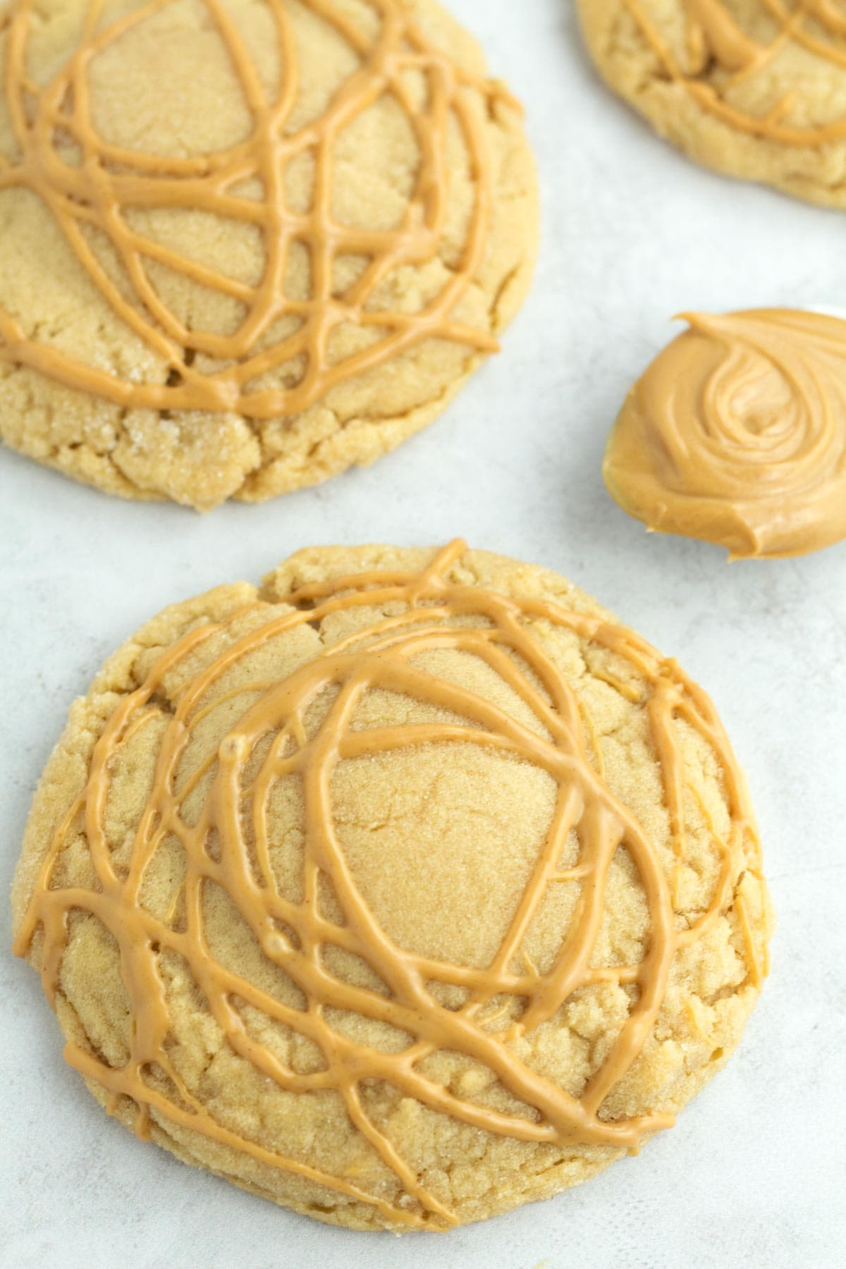 Three cookies drizzled with peanut butter on the counter.