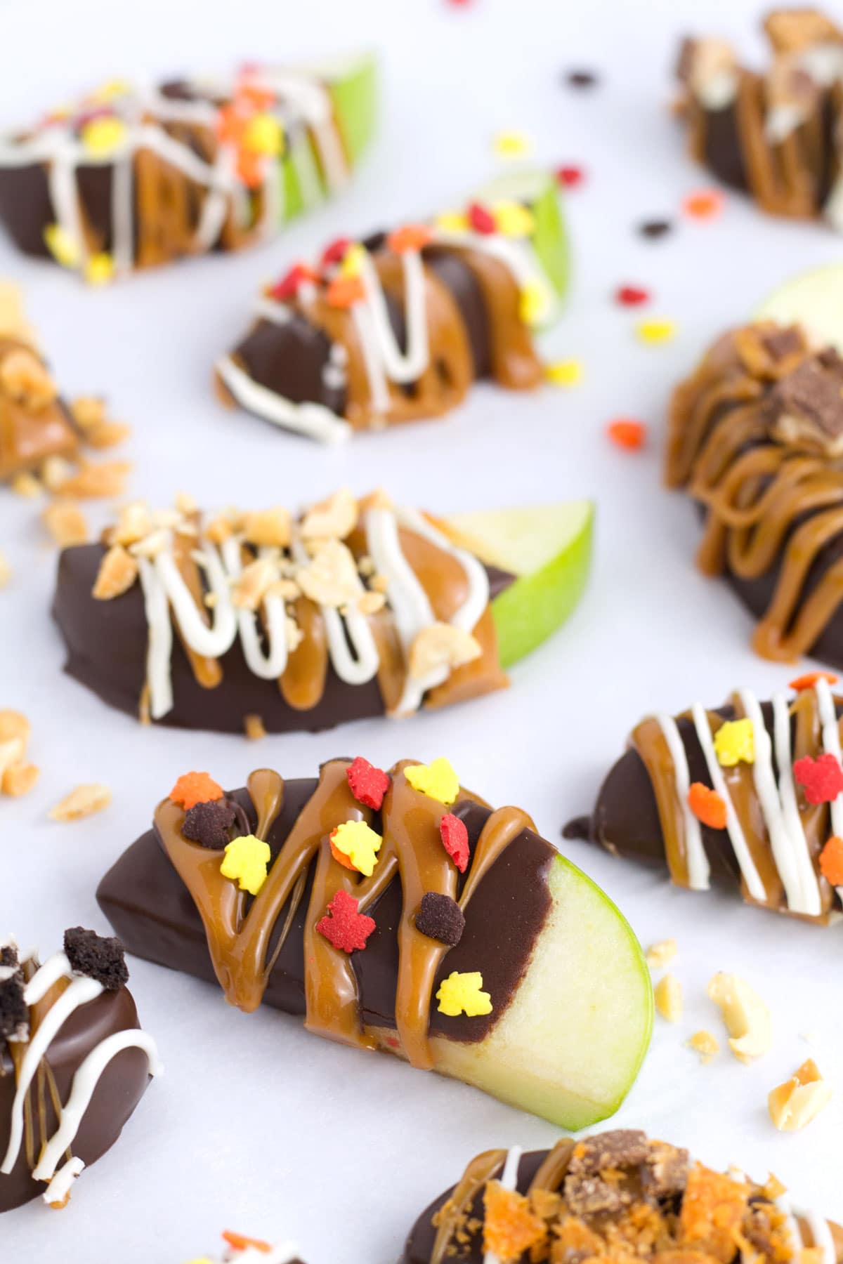 Chocolate covered apple slices with caramel, candy, and fall sprinkles.
