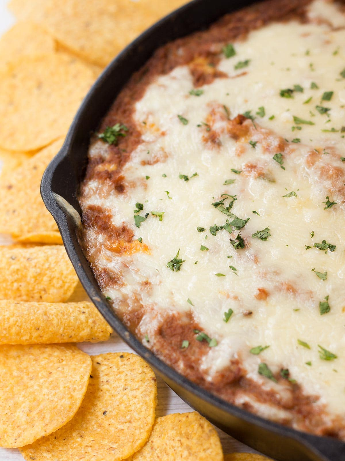Skillet of baked refried beans with cheese on top and tortilla chips on side of pan.
