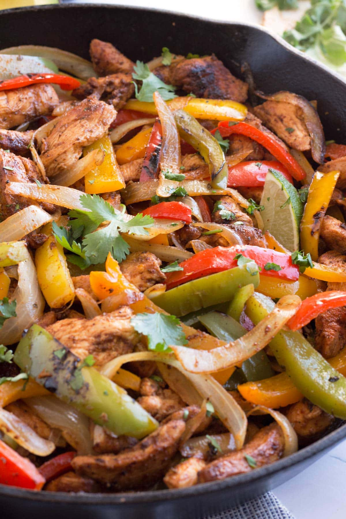 Sizzling fajita meat and vegetables in iron skillet.