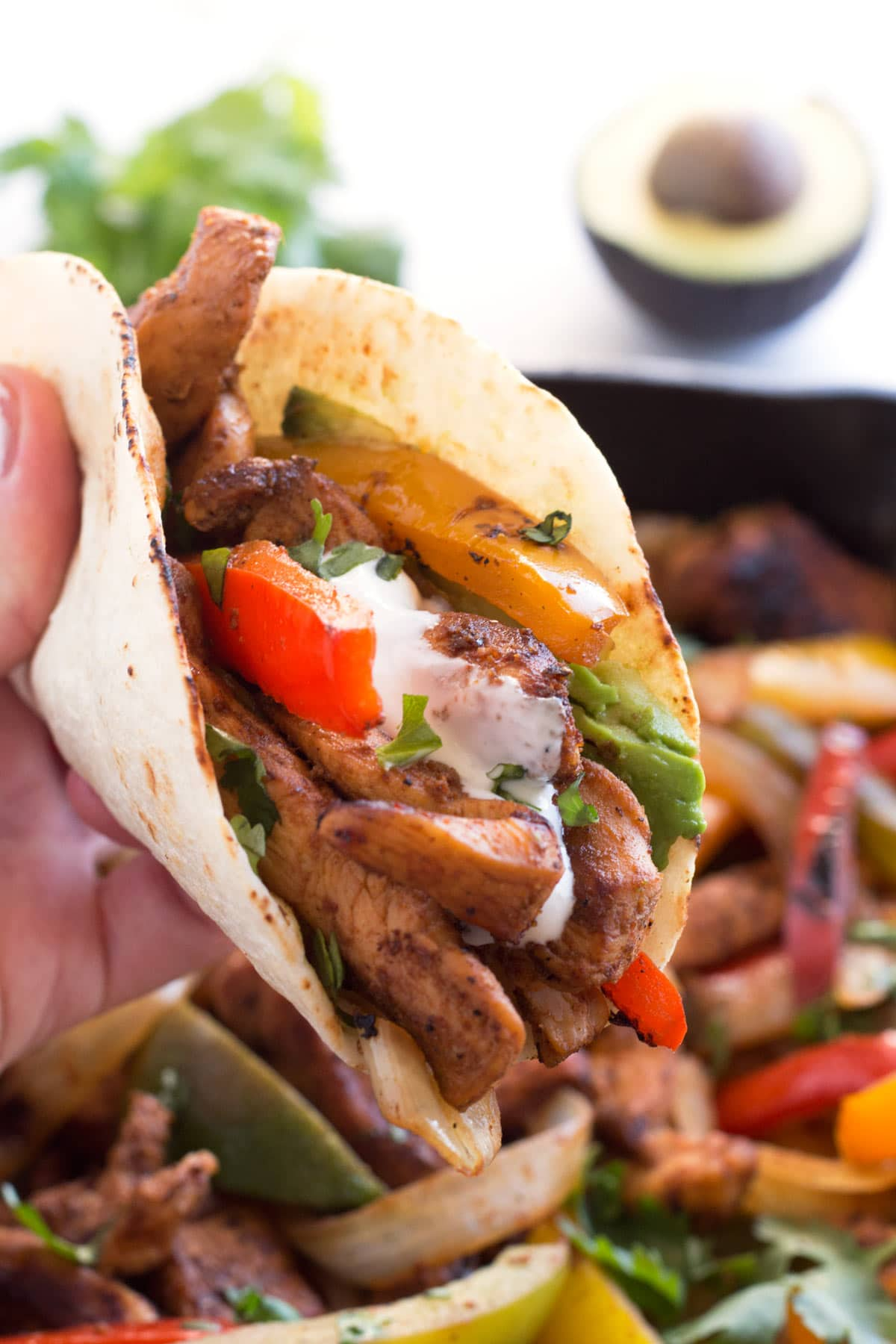 Hand holding fajita filling in a tortilla with toppings.