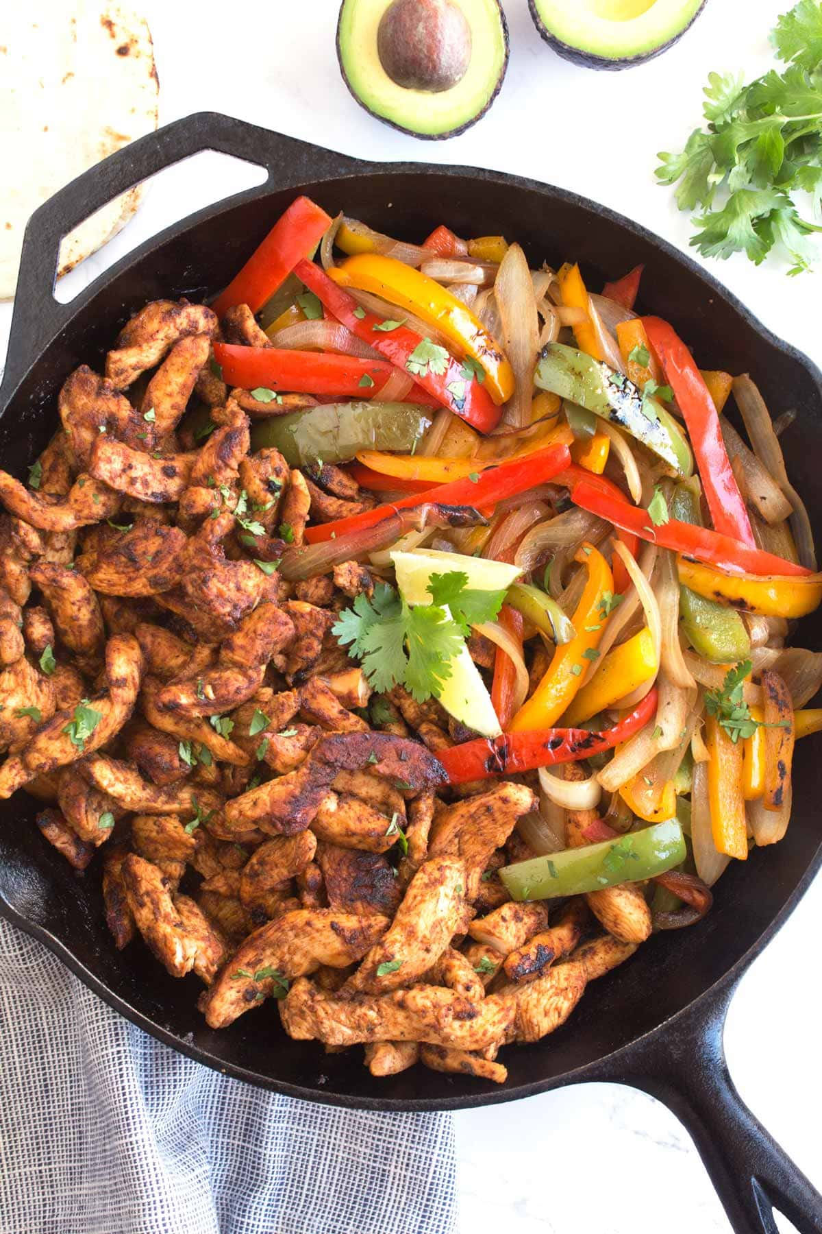 Whole cast iron skillet full of sizzling chicken fajita meat and vegetables.