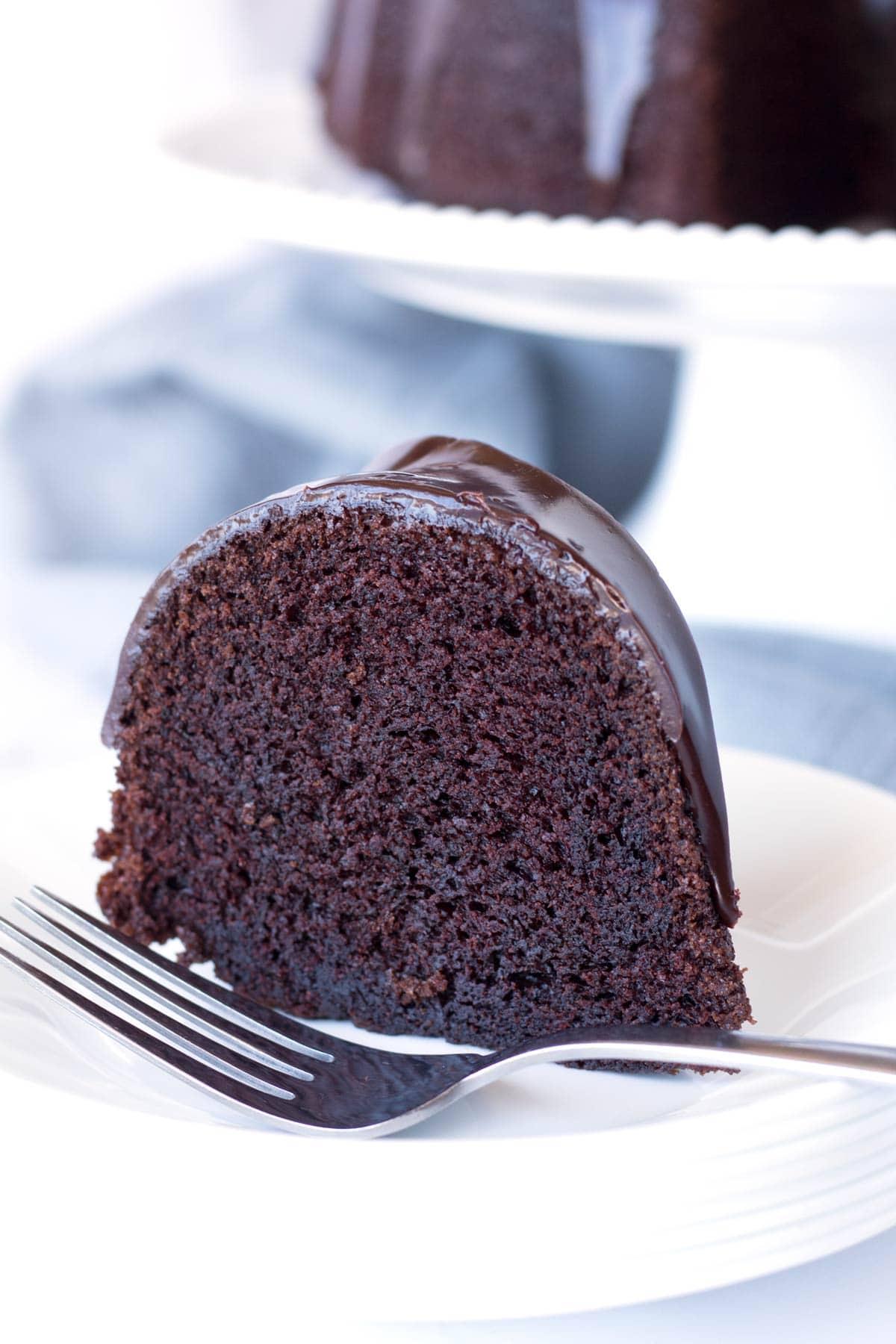 Extra moist chocolate Bundt cake with chocolate ganache on a plate.