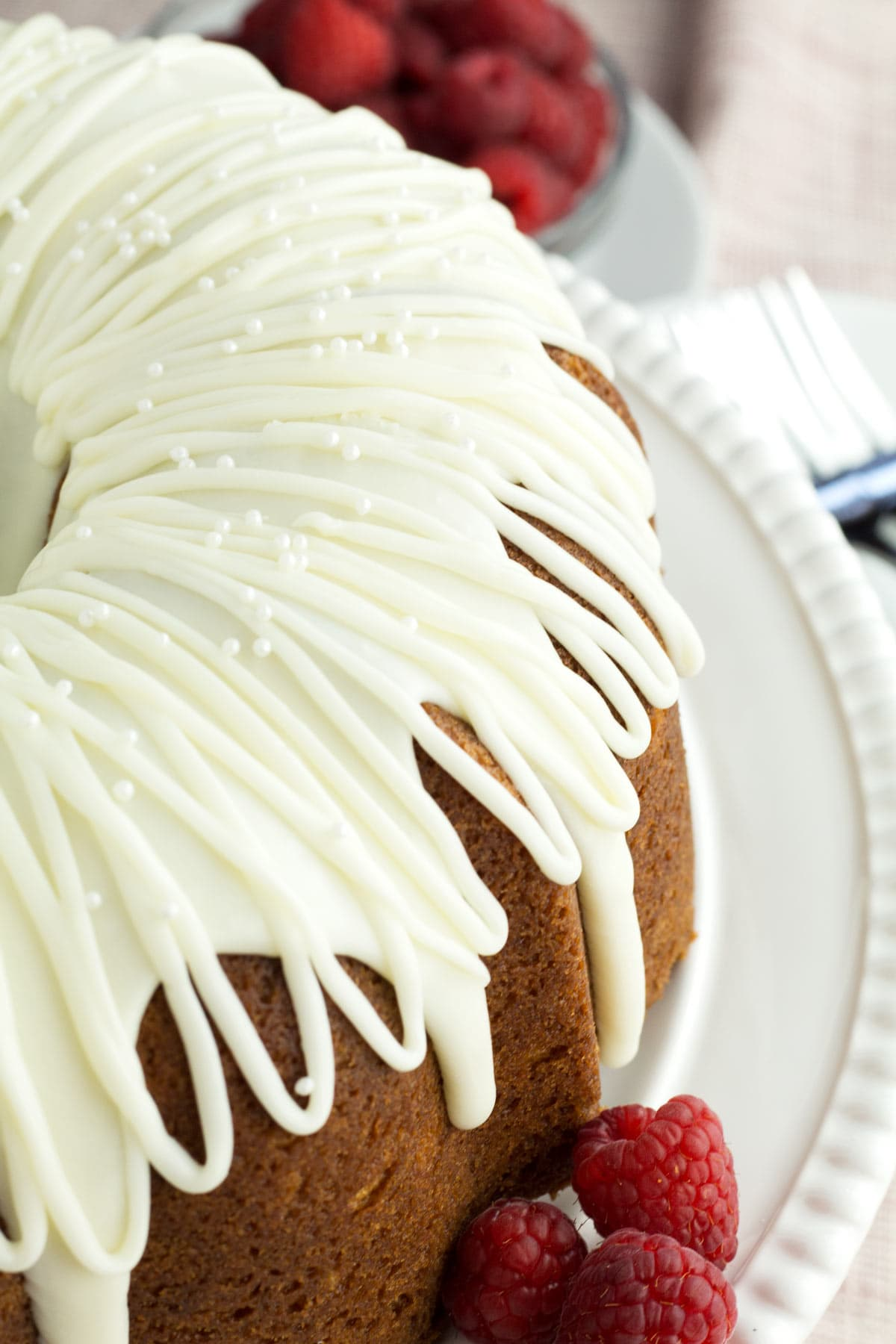 White chocolate frosting piped in loops on a Bundt cake.